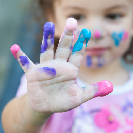 Baby girl is playing with paints outdoors Foto de archivo