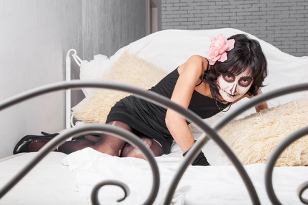 bedstead: Young woman in costume and make-up for Halloween lying on the bed