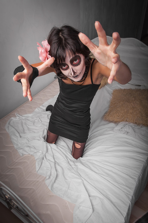bedstead: Young woman dressed as zombie on the bed