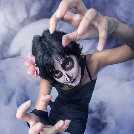 fantasize: Young woman with make-up zombies against smoke
