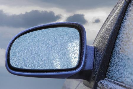Car rearview mirror frozen against cloudy sky