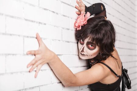 fantasize: Young woman with make-up zombies near the brick wall Stock Photo