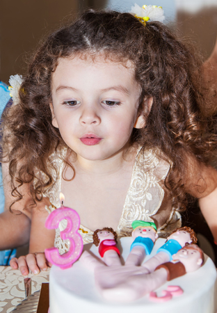 three year old: Three year old baby girl blows out candles on cake on his birthday Stock Photo