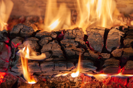 Burning log of wood in a fireplace close-up