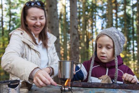 under fire: Muchacho que mira como una mujer enciende un fuego debajo de la taza con agua mineral a partir de fuentes naturales. Centr�ndose en la taza, la gente en el �rea de desenfoque