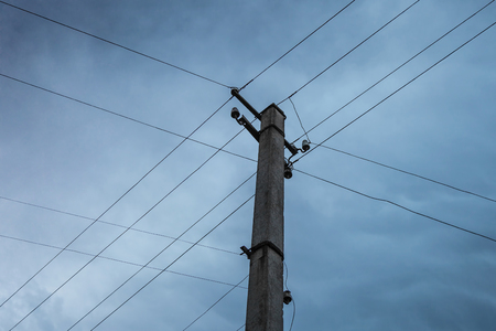 crisscross: Power transmission lines form crisscross pattern around transmission pole on cloudy day. Stock Photo