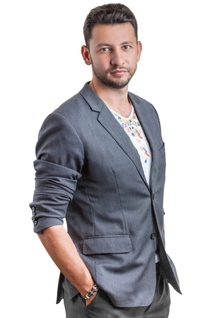 pakistani ethnicity: Middle eastern young attractive man with beard, standing with hands in pockets, studio portrait isolated on white background Stock Photo