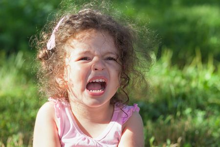 outcry: Photo of crying baby girl outdoors closeup
