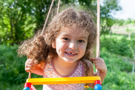 muslim baby girl: Portrait of cheerful baby girl on swing closeup outdoors