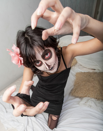 fantasize: Young woman dressed as zombie and makeup for Halloween on the bed pulls his hands up