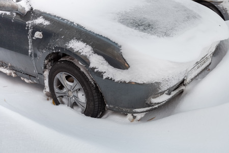 climatic: Car stuck in snow after snowstorm in the winter
