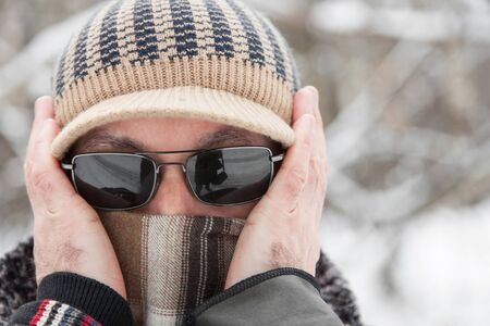 Portrait of an adult man in knitted cap, scarf and sunglasses outdoors in winter day closeup Stock Photo