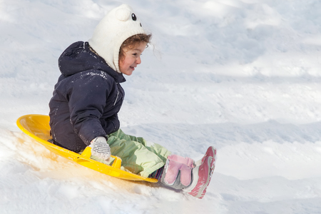 Cute little girl with saucer sleds outdoors on winter day, ride down the hills, winter games and fun Stock Photo