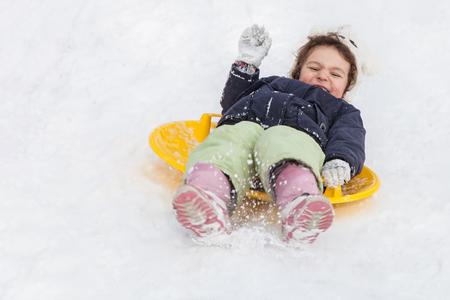 Niña linda con trineos platillo al aire libre en día de invierno, paseo por las colinas, los juegos de invierno y la diversión Foto de archivo