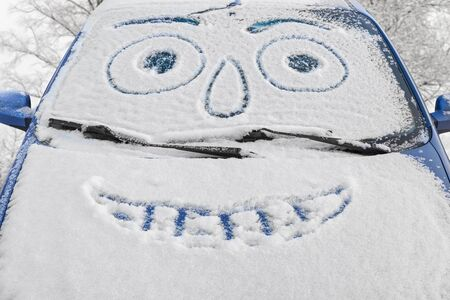 smiley face car: Car covered snow with drawn smiley face in windshield against the backdrop of snowy trees, beautiful winter day Stock Photo