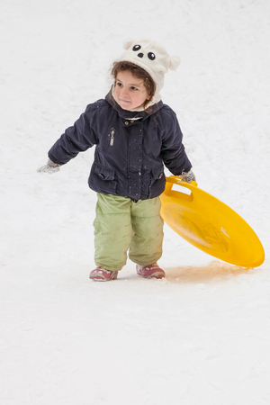 to go sledding: Girl with saucer sleds went up hill in winter, snow, frost, fun and games