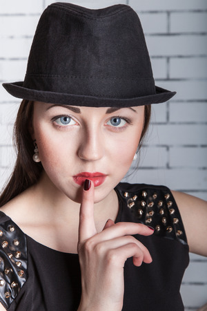 Close-up portrait of young woman in hat with finger on lips, gestures silently, quiet, shhh, secret, facial expression, human emotions, signs and symbols