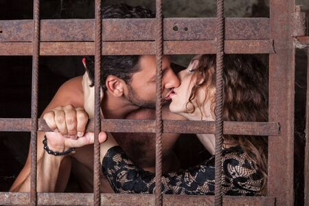 prisoner of love: Young couple kissing behind a lattice, man and woman embrace and kiss on lips of the rusty iron bars