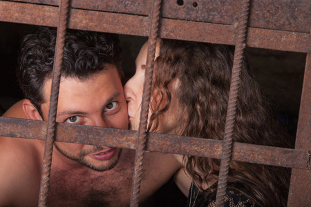 inmate: Young couple kissing behind a lattice, man and woman embrace and kiss on lips of the rusty iron bars