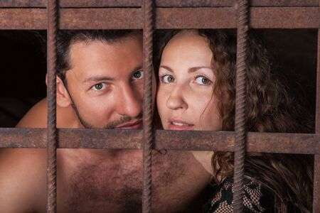 Portrait of a young couple in jail, loving man and woman looking out of rusty iron rods