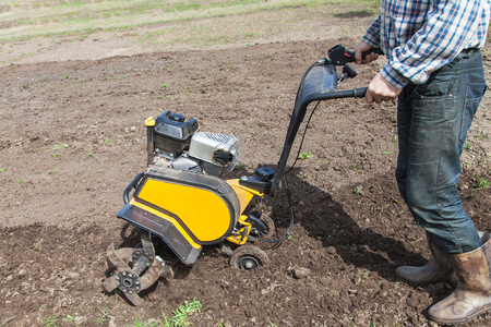 Man working in the garden with garden tiller close-up. Garden tiller to work. Man with tractor cultivating field at spring. Farmer loosens soil by petrol cultivator