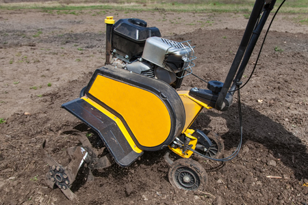 Garden tiller to work, tractor cultivating field at spring, loosens soil by petrol cultivator close-up