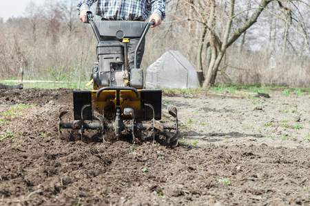Tractor cultivating field at spring, loosens soil by petrol cultivator close-up. Farmer working in the garden with garden tiller.