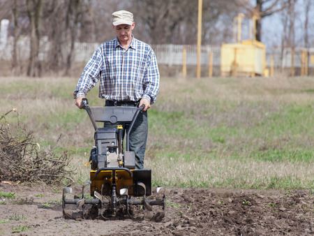 Man working in the garden with garden tiller. Garden tiller to work. Man with tractor cultivating field at spring. Farmer loosens soil by petrol cultivator Stock Photo