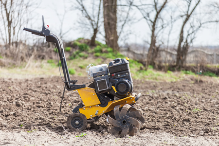 Garden tiller to work, tractor cultivating field at spring, loosens soil by petrol cultivator side view