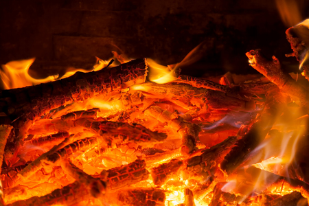 smolder: Burning firewood in the fireplace closeup, texture of fire and flame, dark background Stock Photo