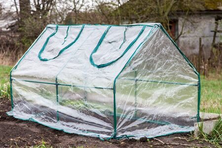 Mini greenhouse for growing seedlings is covered with plastic, installed in the vegetable garden in early spring