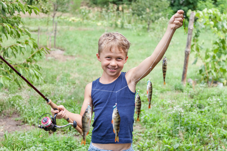 Young angler with tackle bass killer, fisherman boy with fish perches caught on spinning with instantaneous reel