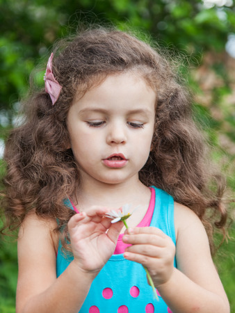 Girl with daisy in her hands, Cute baby girl guesses on a camomile flower Stock Photo