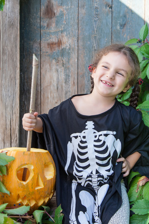 Halloween and celebration concept. Cute little girl in a skeleton suit holds a magic wand and conjures with halloween pumpkin outdoors Lizenzfreie Bilder