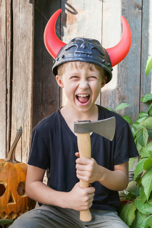 Boy in a Viking helmet with horns holds an ax outdoors, pumpkin halloween in the background