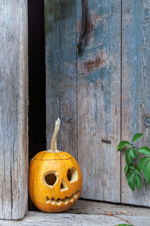 Halloween pumpkin (Jack o lantern) on the background of an old wooden door , ready for text invitation or card for halloween party