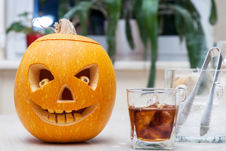 Halloween pumpkin (Jack o lantern) with carved face and glass of whiskey with ice on holiday table