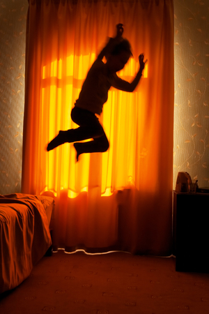 Sleepwalker boy jumps from bed in the moonlit window background, blurred motion Stock Photo