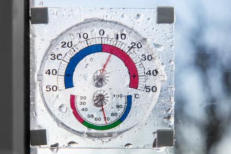 Higrómetro, termómetro todo en uno detrás de la ventana en tiempo lluvioso Foto de archivo - 88991499