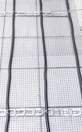 Electric floor heating system installation in new house, electric heating cable is installed on the reinforcement grid with the help of mounting tape on the plates of expanded polystyrene
