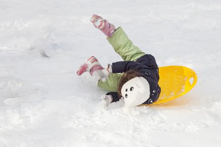 Nettes kleines Mädchen mit Untertasse Schlitten im Freien auf Wintertag, Fahrt auf dem Hügel, Winterspiele und Spaß