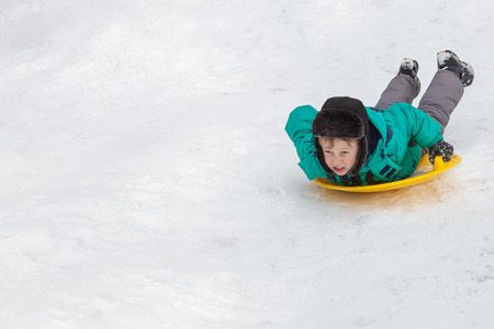 Boy sliding down the hill on saucer sleds outdoors, winter day, ride down the hills, winter games and fun