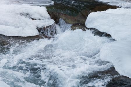 Fluss des Wassers unter dem Eis im Gebirgsfluss in der Winterzeit