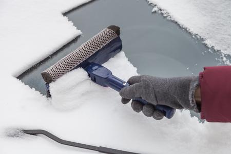 Die Windschutzscheibe des Autos von Schnee und Eis mit Schaber im Winter zu reinigen