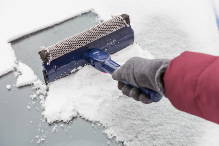 Cleaning the windshield of the car from snow and ice with scraper in winter Standard-Bild