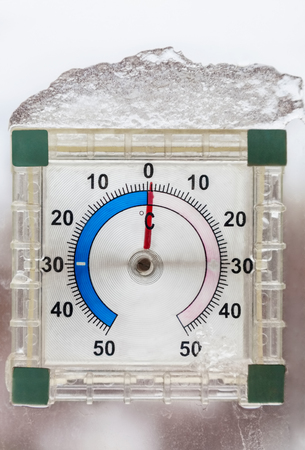 Photo of thermometer outside the window in winter during thaw closeup