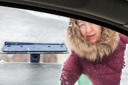 Woman cleans the snow from the car window with a scraper in winter, the view from the inside