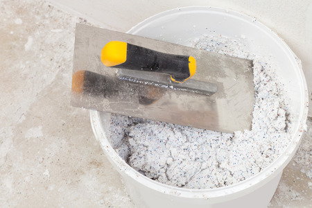 Spatula in a bucket with decorative mineral plaster ready for use