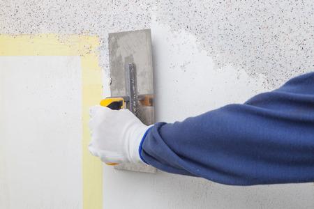 Plastering of walls decorative mineral plaster with a spatula Standard-Bild