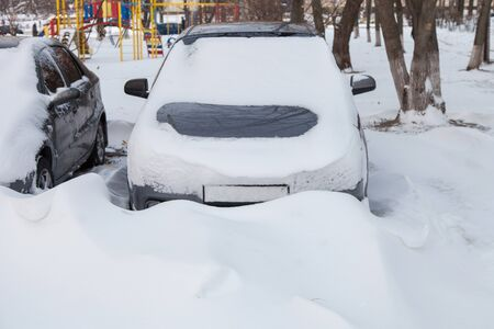 Cars covered in snow in the parking lot after a blizzard